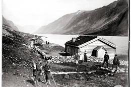 GJENDEBODEN: Gjendebu er den eldste av DNTs hytter som fortsatt er i drift - her besøkende utenfor daværende Gjendeboden i 1878. - Foto: Norsk Folkemuseum