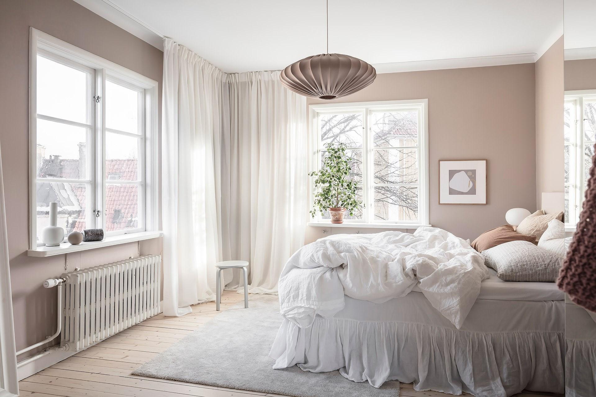 Ljust sovrum med gardiner på gardinskena