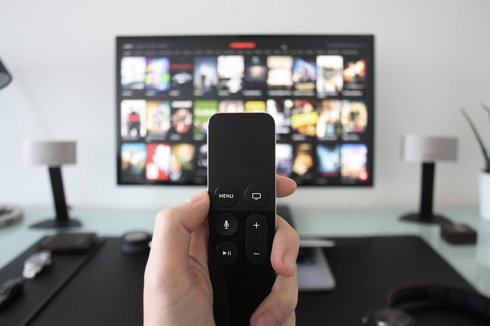 Una persona sujeta un mando para cambiar de canal en su televisor 4K