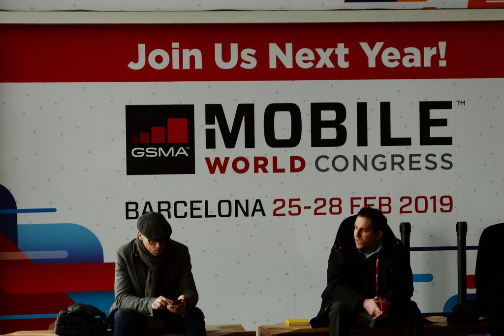 Dos personas están sentadas con un cartel detrás de la Mobile World Congress