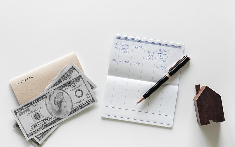 Una libreta está abierta al lado de un bolígrafo y una calculadora