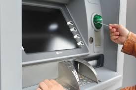 Una persona está introduciendo su tarjeta de crédito en un cajero automático para sacar dinero.