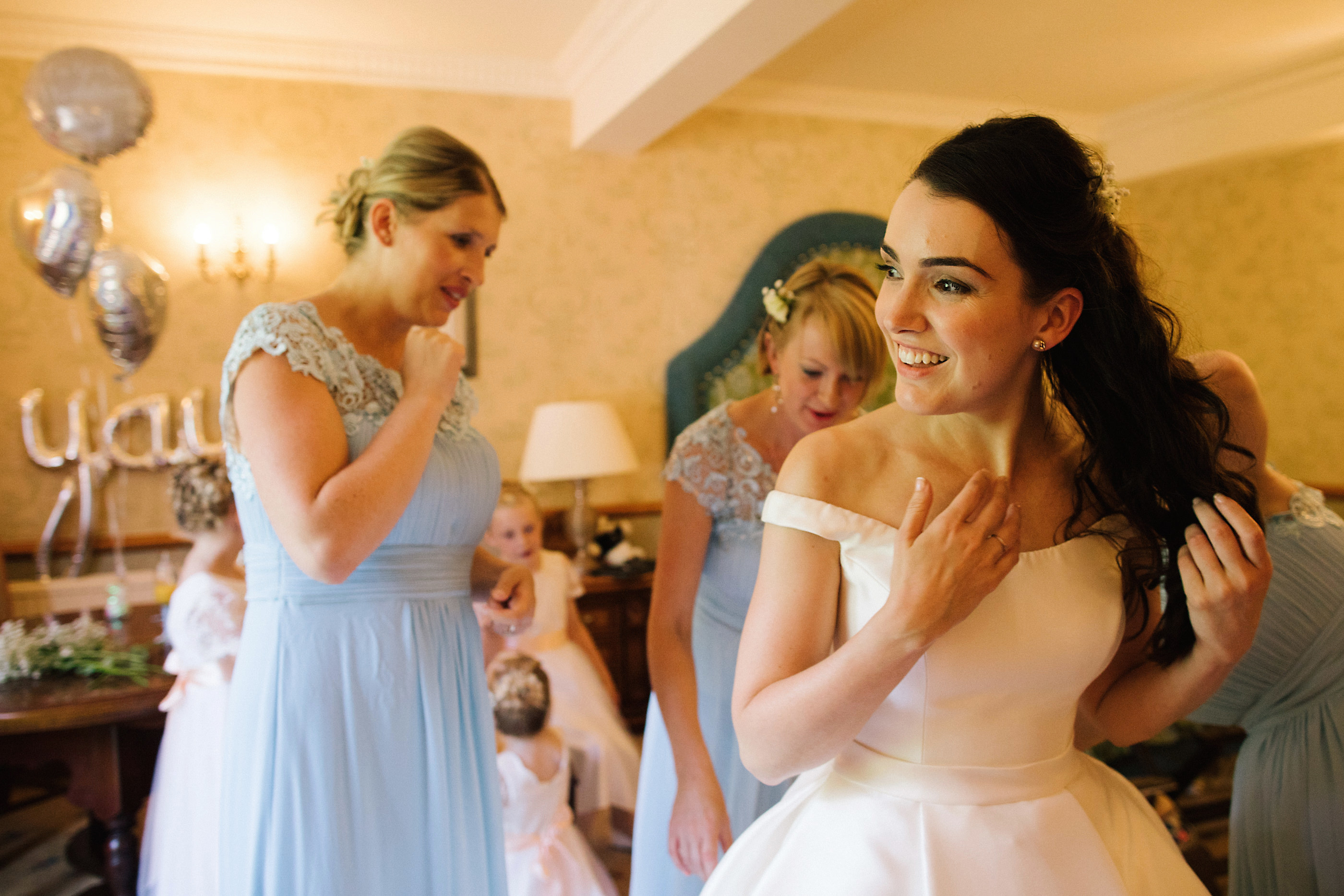 bridesmaids laughing doing up brides dress