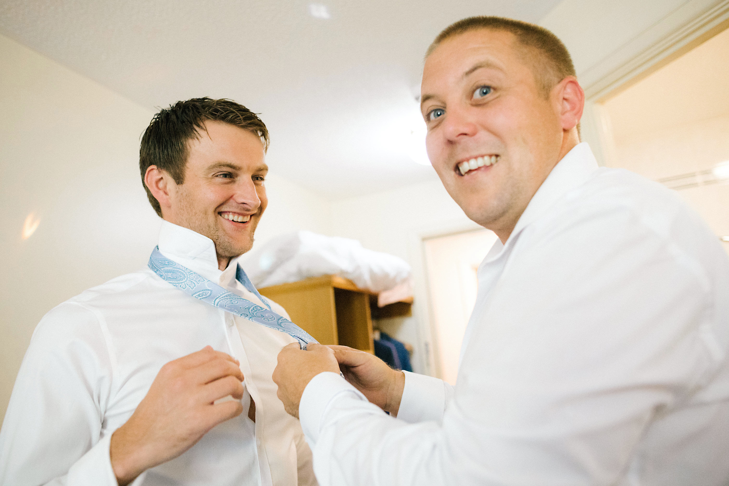 best man doing grooms tie