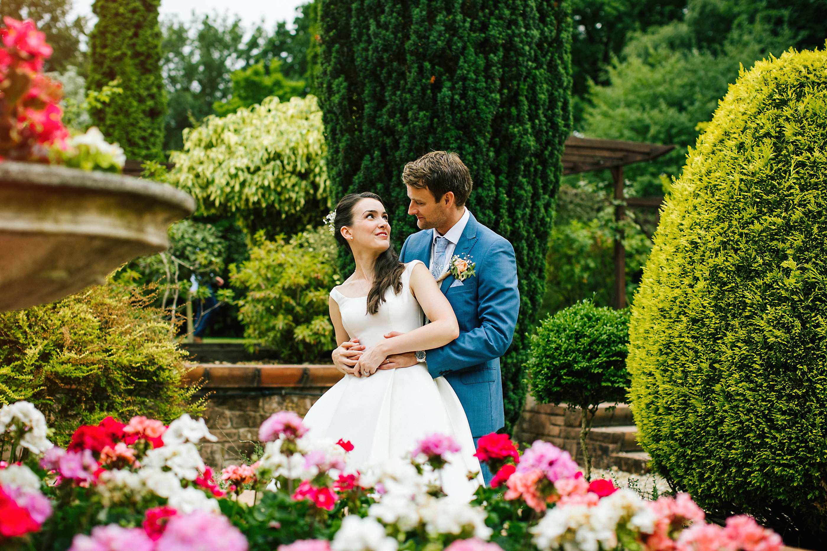 bride and groom in flowers at nunsmere hall