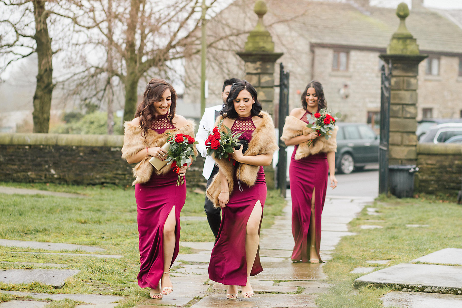 bridesmaids walking through the churchyard