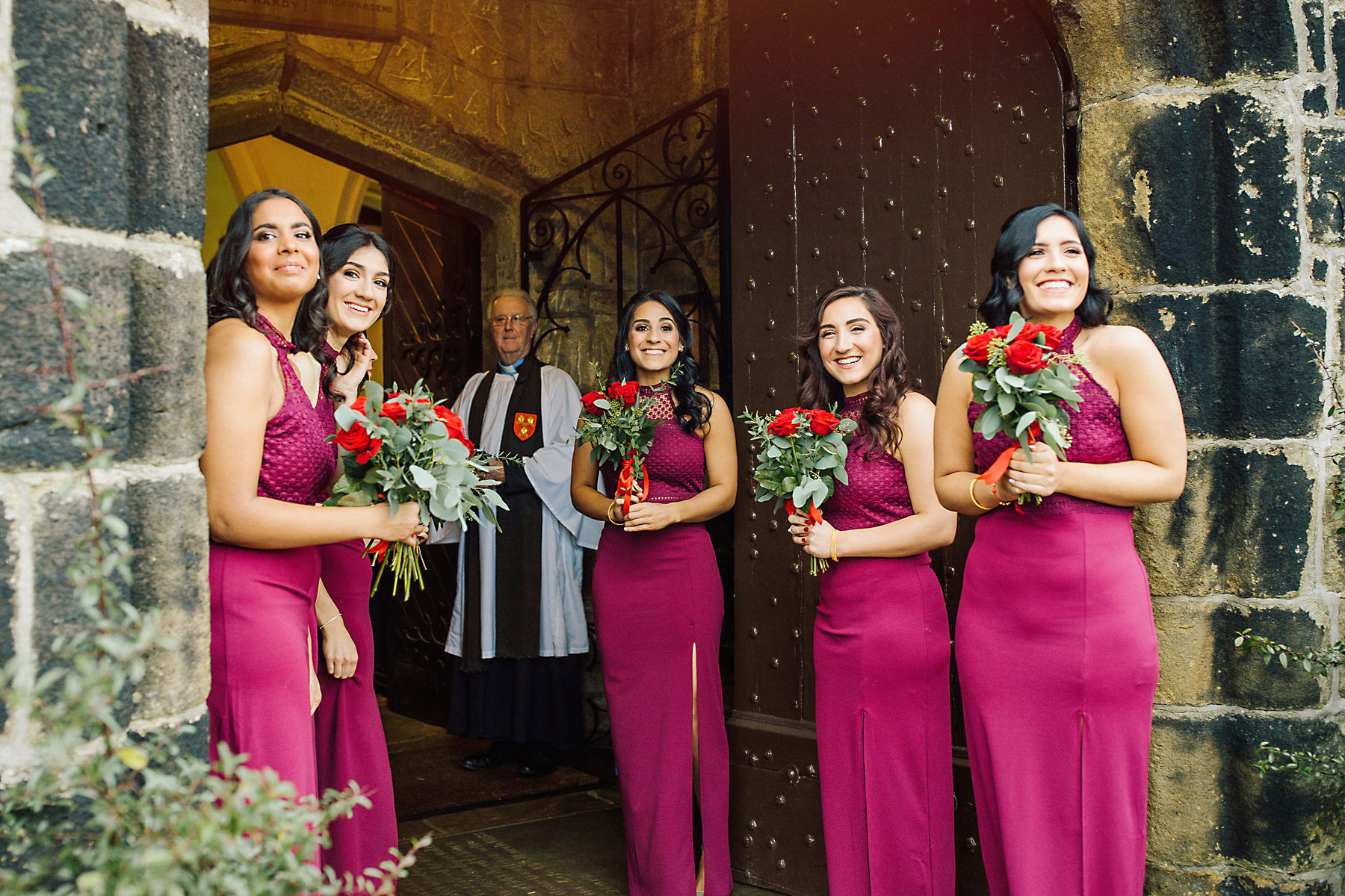 bridesmaids at church door with vicar