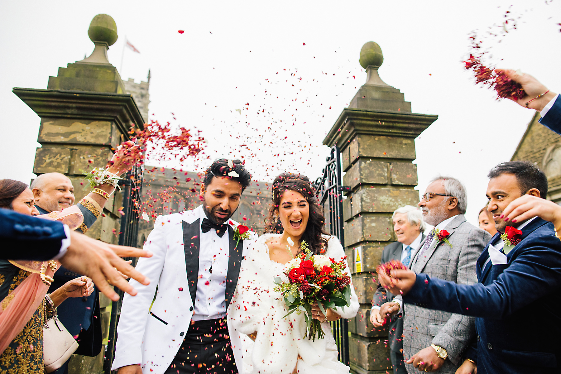 guests throwing petal confetti outside mottram parish church