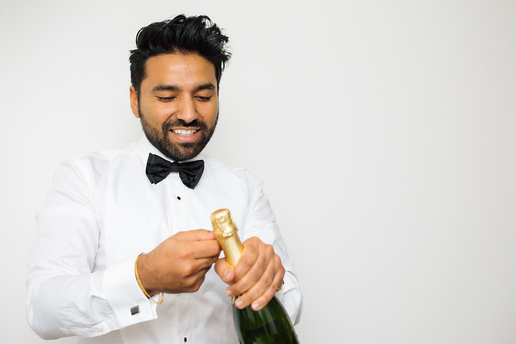 groom opening champagne