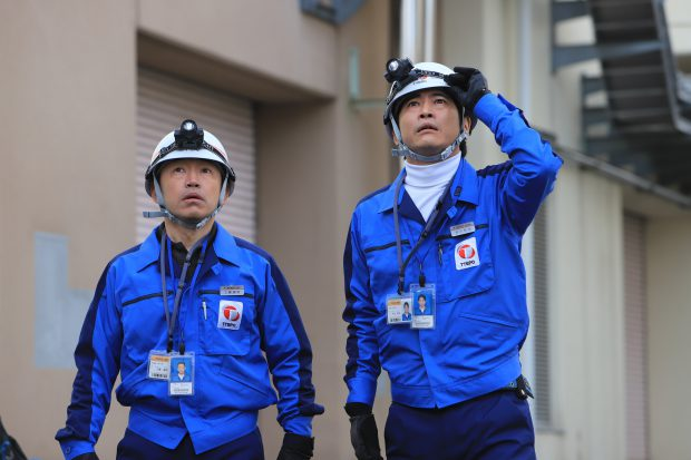 Two workers dressed in bright blue uniforms and white helmets gaze up with mouths open and eyes wide open.