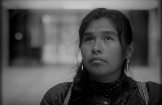 still from Song Without A Name, 2019. This black and white image of a young woman's face and shoulders shows Geo off-centre. Her eyes are looking up, her mouth is turned down, hair tied back but loose around her face