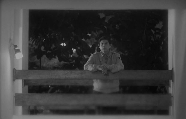 Black and white still from Song Without A Name. A man (Párraga) leans on a railing. He has a cigarette in his left hand.