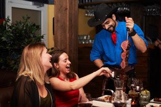 """""""Gauchos"""" kommer til bordet og serverer deg lekkert kjøtt rett fra grillen."""