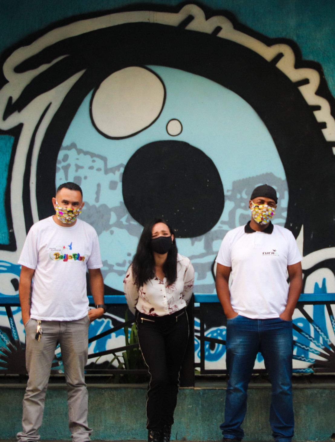 """F.v. Fabio og Ivone (daglig leder) fra Kolibri Brasil.  Alex Camburão (President CUFA de São Bernardo do Campo) foran """"Det sosiale øyet""""-illustrasjonen på Kolibri Kommunikasjonssenter."""