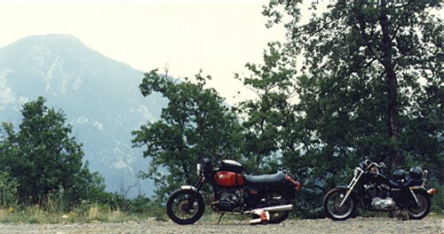 A BMW, a Sportster, and a mountain. The Sportster is the least suitable of the three for sitting on all day.