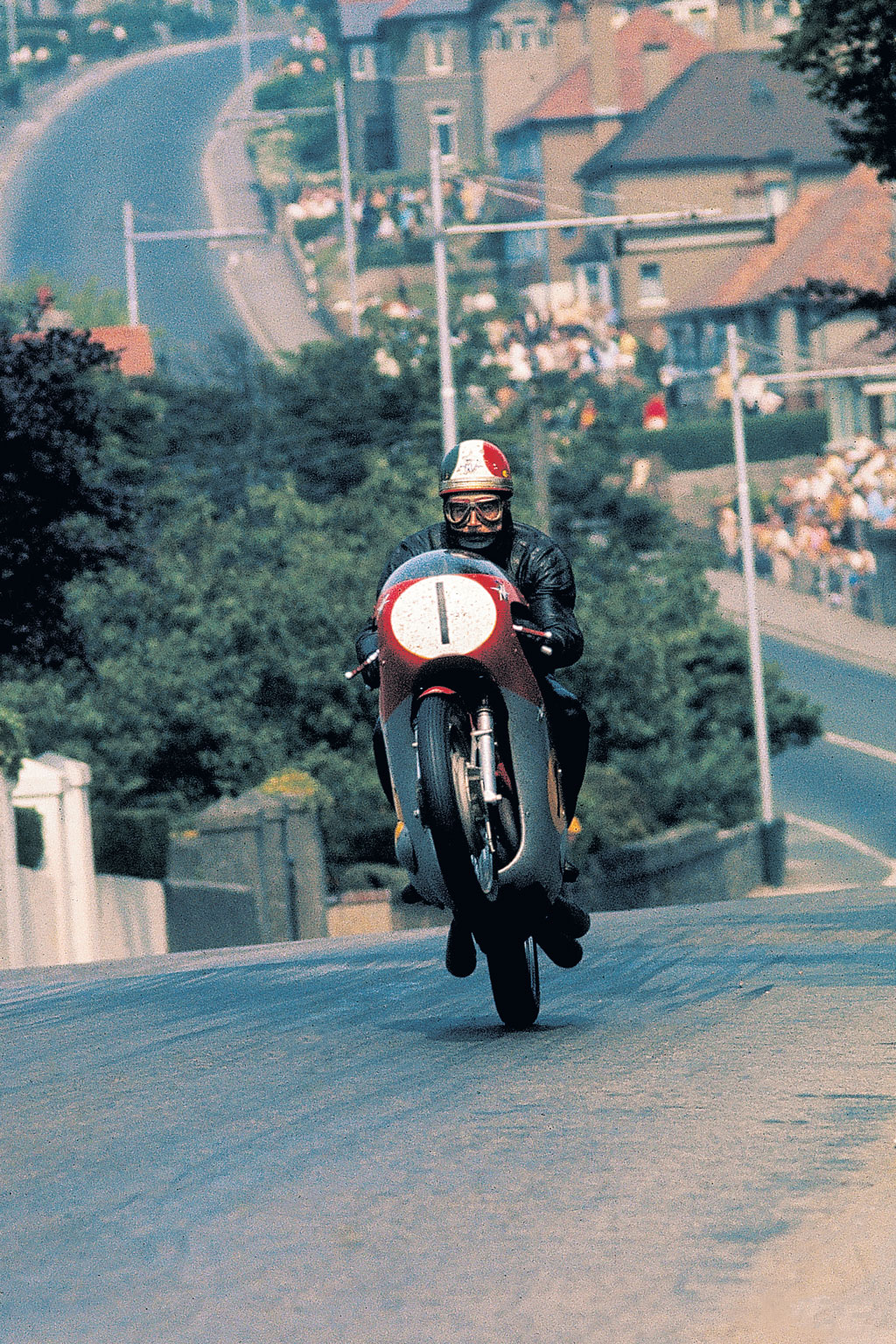 Surely one of the most iconic TT shots, captured by the camera of Nick Nicholls, Italian legend Giacomo Agostini crests the rise at the foot of bray Hill which was forever after know as Ago's Leap.