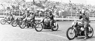 Harley-Davidson v-twins line up for start of dirt track race