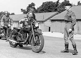 Trainee Dispatch Rider undfer the beady eye of instructor pushes his Matchless G3L classic motorcycle during the Second World War