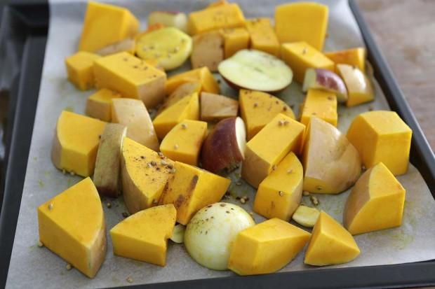 Kürbis, Apfel, Zwiebel und Knoblauch mit Gewürzen auf Backblech