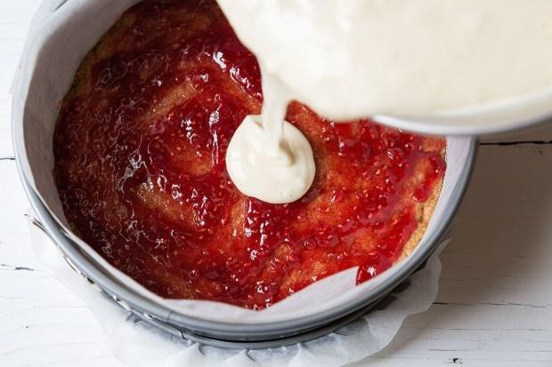 Frischkäse-Füllung auf Cakeboden mit Himbeerkonfitüre verteilen