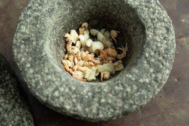 Getrocknete Crevetten mit Knoblauch und Palmzucker im Mörser zerstossen