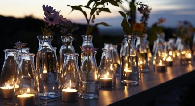Schnell, günstig und einfach: Reihungen von Gläsern auf Mäuerchen, Simsen und Tischen, in denen Teelichter oder Einzelblumen stecken. Bild © www.deavita.com (CC BY-ND 3.0)