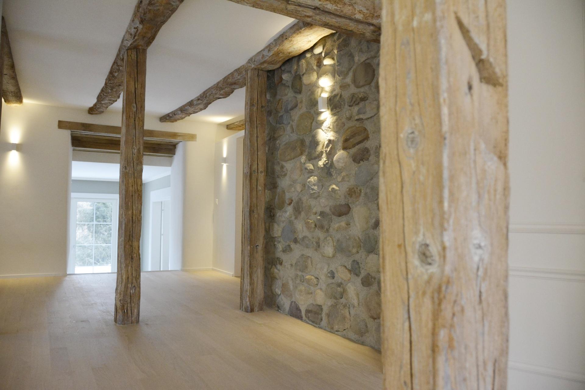 Lasierte Sichtbalken und eine Steinwand, die wie eine Aussenmauer gestaltet ist, verleiht Charakter.