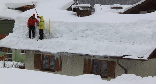 Ein Hausdach wird von den Schneemassen befreit.