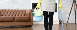 Eine Frau steht bereit, um die Bödener einer elegant eingerichteten Wohnung zu reinigen.
