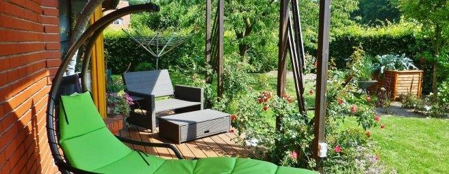 Eine grüne Liege steht auf einer Terrasse vor einem Backsteinhaus in der Sonne.