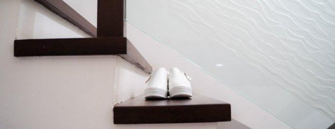 Ein Paar weisser Schuhe befindet sich auf einer Treppe mit dunklen Stufen in Seitenansicht.