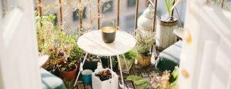Balkon mit weissem Tischen und vielen Pflanzen im Shabby-Chic-Stil.