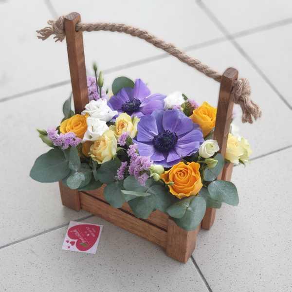 Анемоны, статица и кустовая роза в деревянном ящике