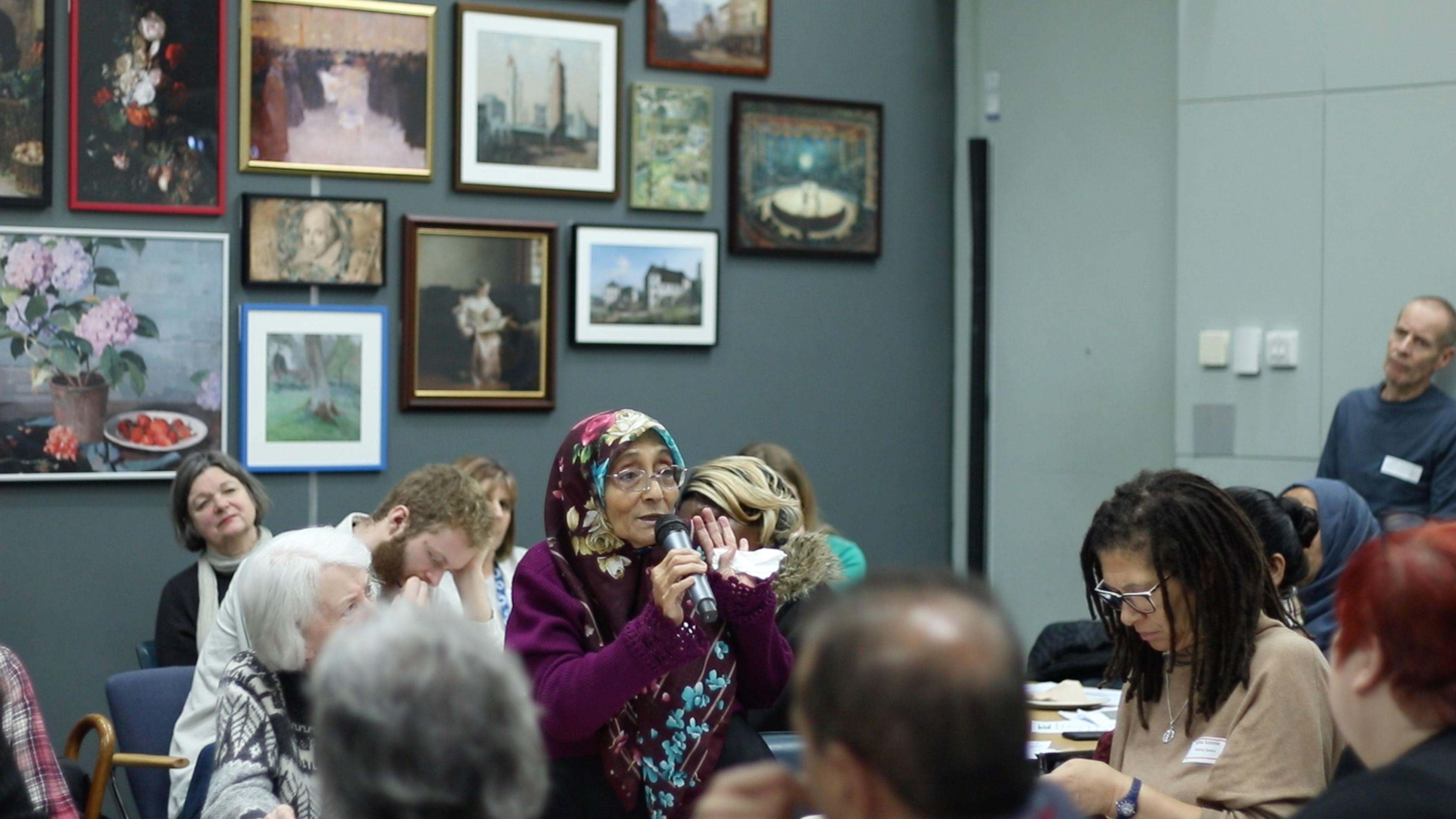 older Asian woman speaking with microphone at event paintings on wall behind