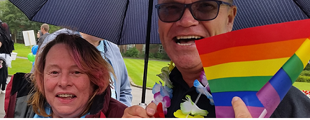 smiling woman and smiling man with rainbow flag