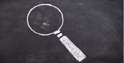 drawing of a magnifying glass on a blackboard