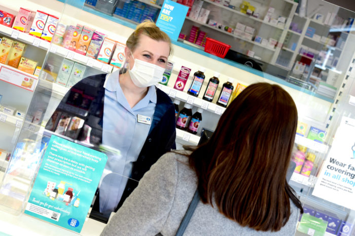 CHECK-WITH-COMMS-BEFORE-USE-Colleague-in-Pharmacy-with-mask-behind-screen-1.jpg