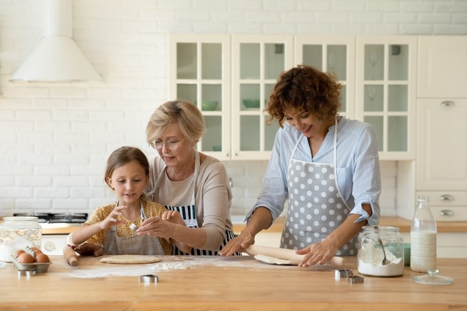 Three generations grandmother mother daughter cooking in kitchen