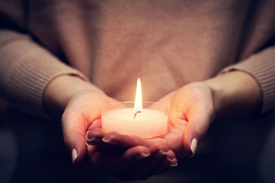 Woman's hands holding candle memorial