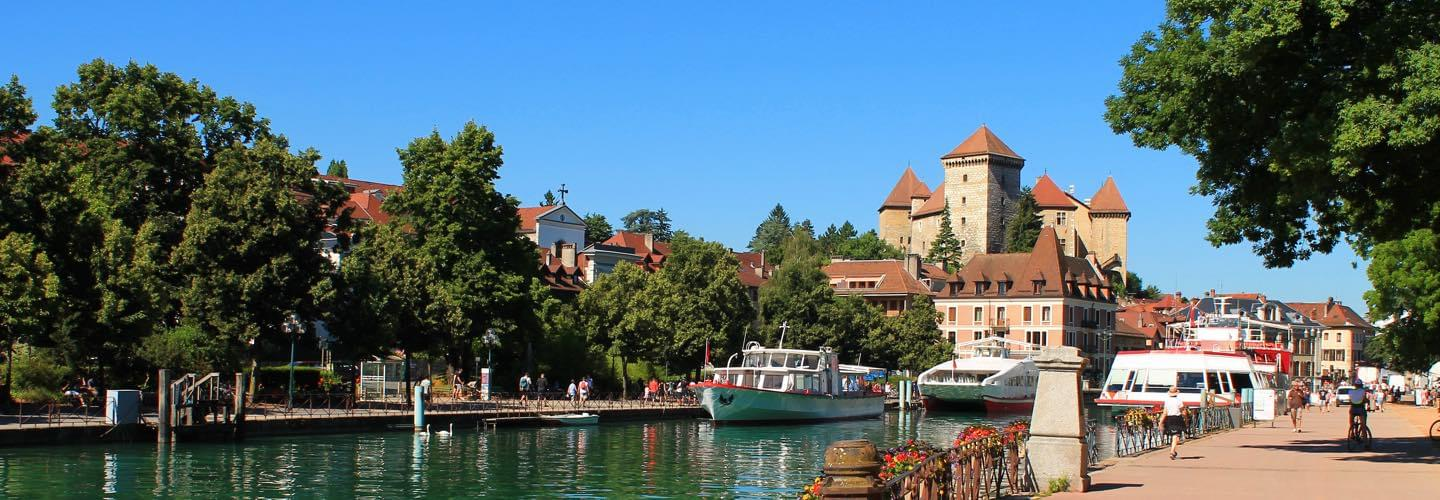 Annecy lake channel with trees and boats and the Church Notre-Dame-de-Liesse