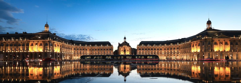 Bordeaux's place de la Bourse with a tramway reflected in the Miroir d'eau at sunset