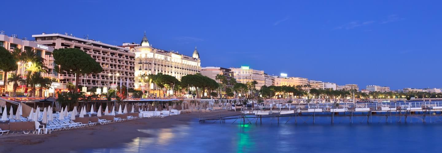 A private beach in Cannes by night with the illuminated Intercontinental Carlton palace on the Croisette
