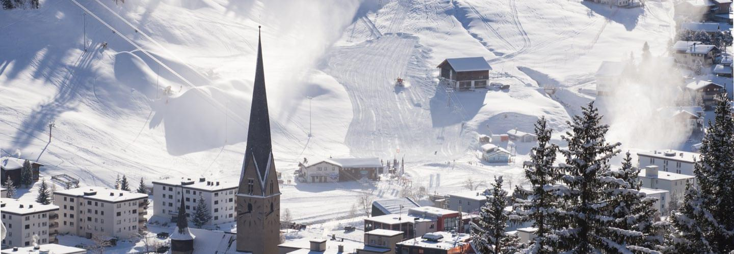 Skyline view of Davos with snowy slopes ski chalets and the steeple of the church