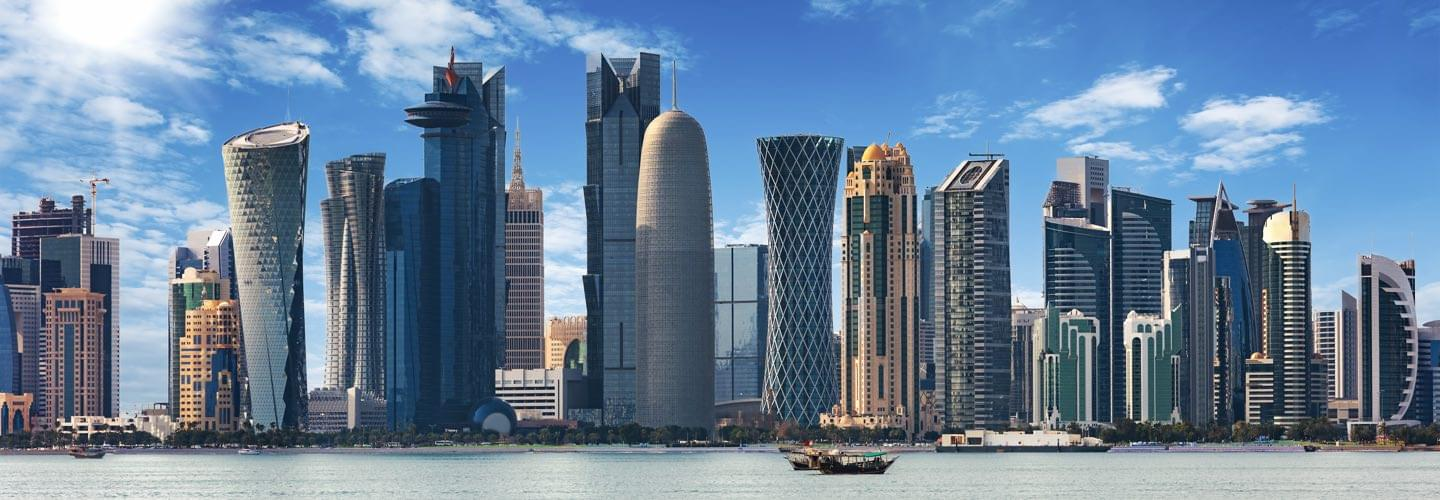 Skyline of Doha capital city of Qatar with skyscrappers and the sea by daylight