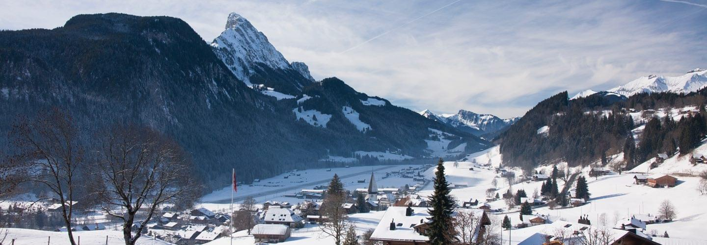 Skyline of Gstaad in Switzerland with rooftops covered in snow and mountains