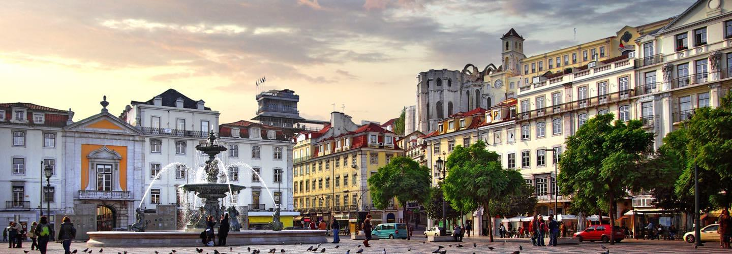Skyview of Rossio square in Lisbon in the sunset with trees and people walking by