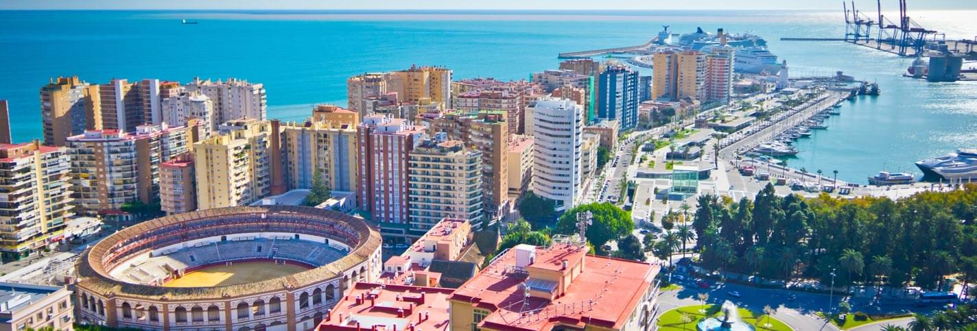 Sunny view of Malaga and its Malagueta bullring with the sea and harbour in the background
