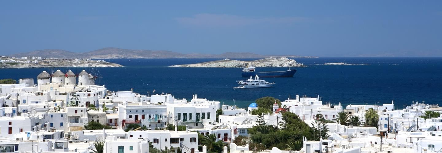 White house with Mediterranean sea in background and a yacht and an ocean liner in summer