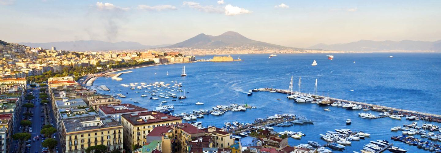 Naples port in summer with boats and the Mediterranean sea and mount vesuvius in the background