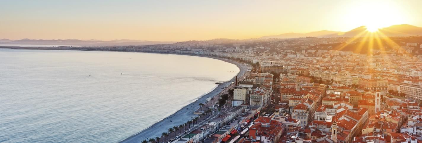 Sunset in Cannes with Promenade des Anglais and surrounding buildings and the Mediterranean sea